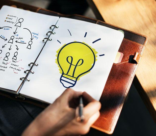ノートに光った電球の絵。ひらめきの図
