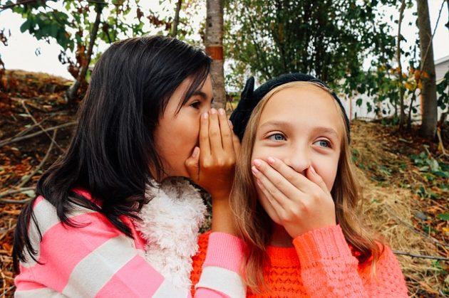 女の子が別の女の子の耳にナイショ話をする写真