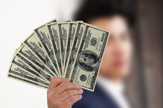ドル札を手に持つ人