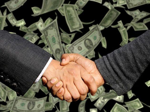 握手の写真。背景に紙幣